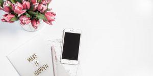 Mesa de escritório com flor e celular para redes sociais